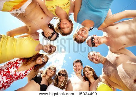 Below view of circle of friends looking at camera with blue sky above them