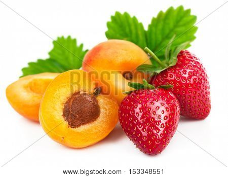 Fresh fruits healthy food berry mix strawberries with apricots green leaves. Isolated on white background
