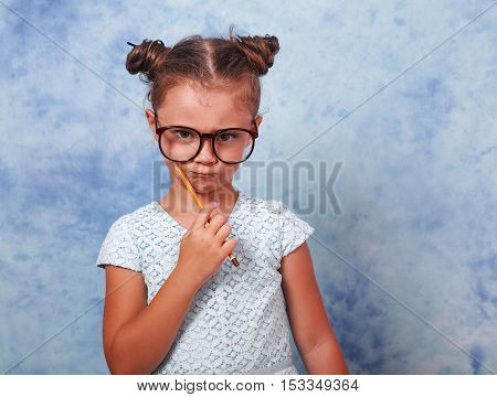 Serious Strict Kid Girl In Eye Glasses Holding Pencil And Thinking About With Trendy Hair Style On B