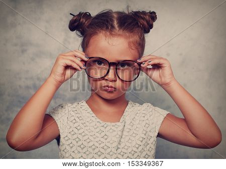 Serious Angry Kid Girl With Modern Hair Style In Fashion Glasses Looking And Holding The Eyeglasses