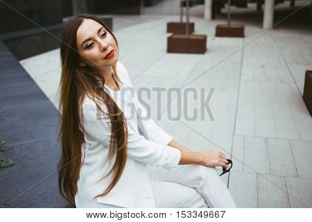 Stylish female with red lipstick is resting at outdoor square between work break. Copy-space area for your text or design