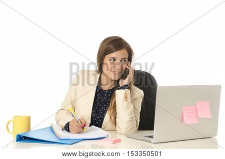 corporate portrait of young attractive businesswoman on her 30s sitting at office chair working at laptop computer desk talking on mobile phone taking notes writing on pad