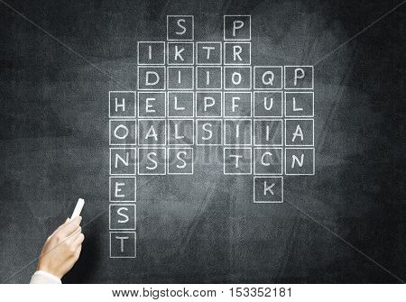 Studying concept with crossword drawn with chalk on blackboard
