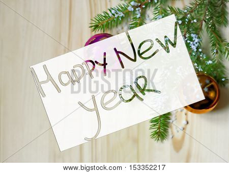 Greeting card to celebrate the New Year. Blurred background a wooden surface fir branches and Christmas decorations as symbols of the New year.