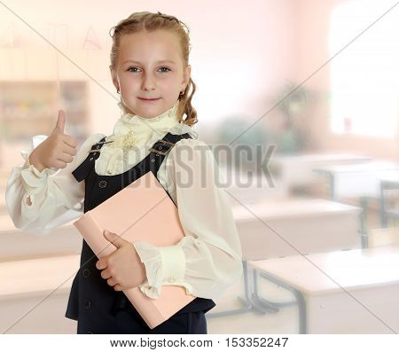 Dressy girl schoolgirl in black dress and white blouse holding a textbook and shows thumb. Gesture all right. Close-up.During a lesson in school.