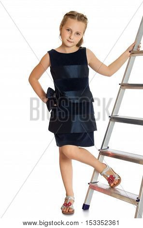 Nice little girl in a fashionable dress. The girl put her foot on the ladder. Close-up -Isolated on white background