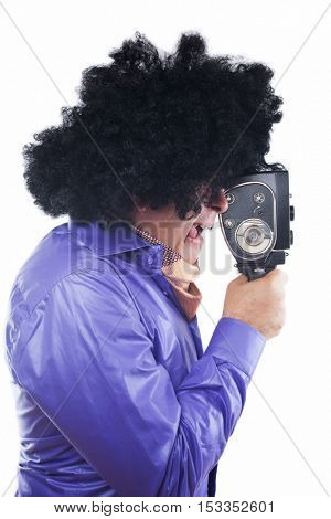 Man with black afro wig using vintage movie camera isolated on white background