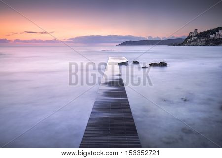 Castiglioncello travel destination wooden pier in the bay rocks and sea on sunset. Tuscany Italy Europe. Long Exposure