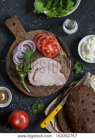 Ingredients for cooking sandwich - roasted pork tomato red onion arugula rye bread soft cheese. Top view on dark background