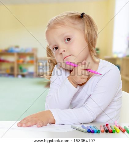 The concept of pre-school education of the child among their peers . on the background of the playroom with shelves for toys. Montessori.Pretty little blonde girl drawing with markers