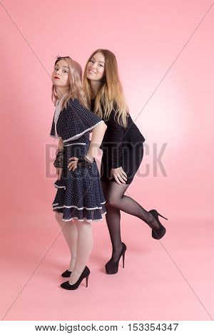 portrait of two girls on a pink background
