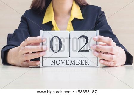 Closeup white wooden calendar with black 2 november word in blurred working woman hand on wood desk in office room selective focus at the calendar