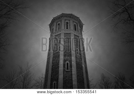 a frame from old movie. black and white. old tower and trees. mystic. horror. thick clouds