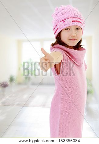 Cheerful little girl in a pink knitted dress and hat, shows hand gesture all right, thumb to the top. In the room with the big bright window in the wall.