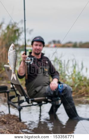 Fish caught on a hook with fisherman on background. Selective focus.
