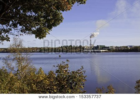 Miramichi, Catham, NB, October 15, 2016 -- Wide view of large industrial building with smoke stack spewing a cloud of bilious smoke framed by trees on the left on a bright sunny day in October. Shot is taken from the Miramichi looking across the Miramichi