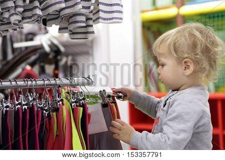 Serious Boy Choosing Clothes