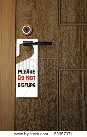 3D : Illustration of white Paper signboard with Please do not disturb text hanging on a handle of wooden door resort or hotel