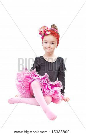 Image of little dance girl in pink tutu on isolated background sits in dancing pose and smile to the camera