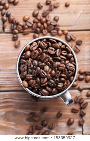 Roasted Coffee Beans In Cup On A Brown Wooden Table