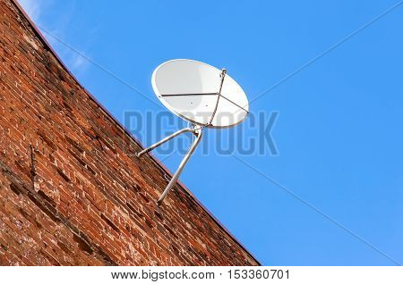 Satellite dish mounted on the grunge brick wall of house
