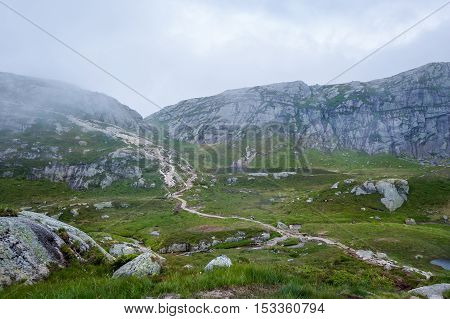 Scenic hiking path to famous Kjerag stone through the rocks and hills. Lysefjord, Norway.