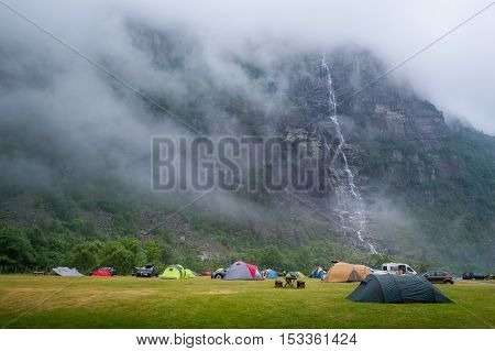 Tents at Lusebotn camping with amazing view on the rocky mountain in fog and high waterfall. Lysefjord, Norway.