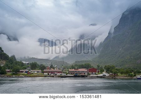 Lusebotn norwegian village under the mountain range in clouds and fog. View from the Lysefjord ferry, Norway.