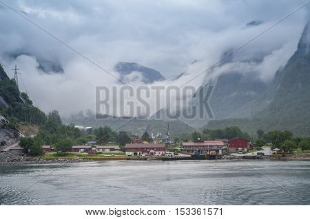 View from Lysefjord ferry to the Lusebotn. Mountain landscape and town on the fjord coast, Norway.