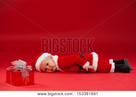 Beautiful little baby celebrates Christmas. New Year's holidays. Baby in a Christmas costume with gift It lies on a red background