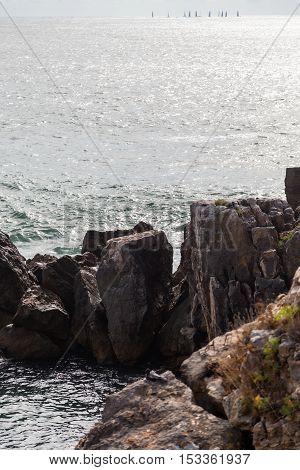 surf ocean rocks with sails on horizone
