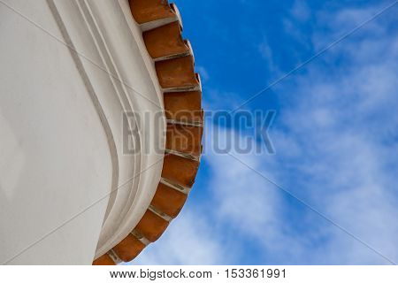 from bottom view on edge round roof of old house with red tiles on background of sky