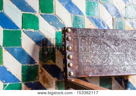 antique interior with azulejo tiles on wall and back of chair with ornament on leather