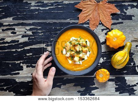 Roasted pumpkin and carrot soup with cream and croutons for Thanksgiving, halloween. On creative dark wooden background. Copy space. Top view.