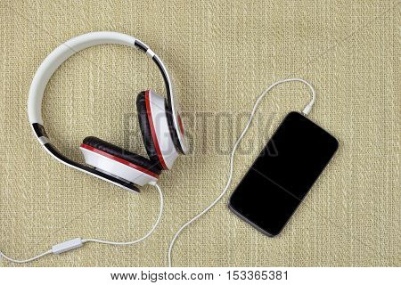 Smatrphone and headphones on a rough sacking background. Top view. Modern technology in our lives. Listen to music.