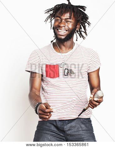 young handsome african american boy singing emotional with microphone isolated on white background, in motion gesturing smiling close up