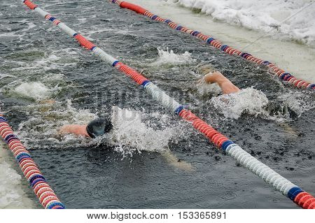 Tyumen, Russia - February 5, 2005: The club of winter swimming holds competitions in the 25 meters ice-hole. Men swim