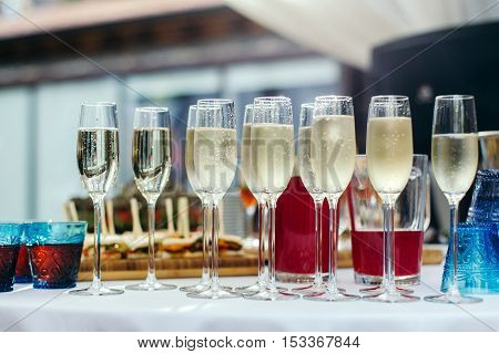 Champagne poured into glasses stands on the table covered with a white tablecloth.