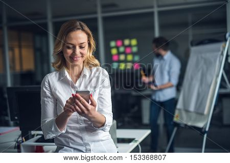 Businesswoman texting on a mobile phone in the office.