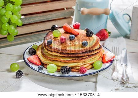 Tasty pancakes with maple syrup and fruits on old wooden table