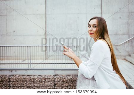 A stylish girl with nice make-up and red lipstick is wearing white suit. Woman is standing outdoors and using a smartphone while standing on a street. Copy space area for your text and design