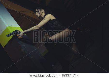 Military brunette girl with gun in a garage in attitude shoot, dressed in bulletproof vest