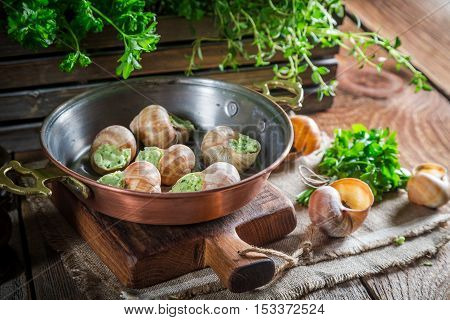 Delicious snails before roasting on old wooden table