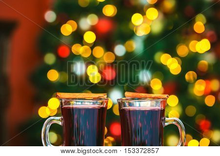 Beautiful Two Glasses Of Mulled Wine On Bokeh Background Decorated Christmas Tree. The Idea For Post