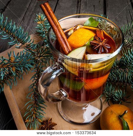 Christmas mulled wine with the addition of fragrant spices, apples, mandarins and oranges. With Christmas tree branches and pine cones.