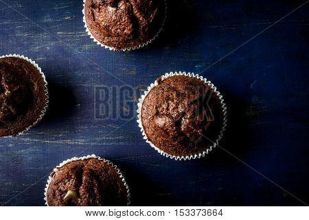 Freshly baked chocolate muffins with lemon kurd inside, on a dark blue wooden table.  Copy space, top view