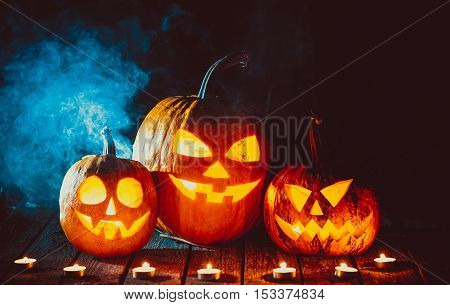 Three Glowing Pumpkins Symbolizing The Head Of Old Jack, With Smoke On Wooden Background. Soft Focus