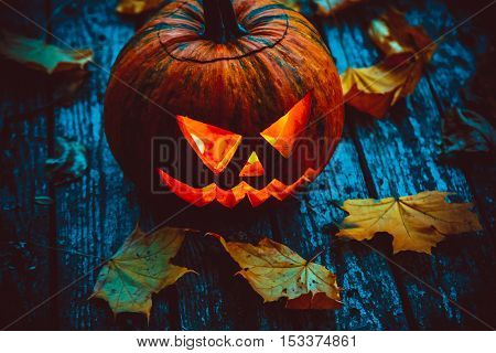 Glowing Pumpkin Symbolizing The Head Of Old Jack, With Autumn Leaves On Wooden Background. Soft Focu