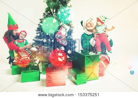 Happy family decorating Christmas tree, dressed in elf and Santa helper costumes. White background with copy space. Family decorating Cristmas tree. Merry Christmas 2016 New Year 2017