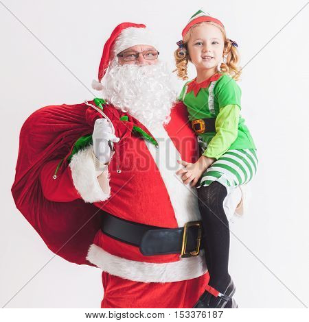 Christmas Wish 2016. Santa Claus and Little Girl dressed in Elf costume. Telling Wishes in Santa Claus's Ear. Cristmas Scene at White Background